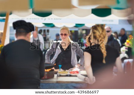 Beautiful blonde caucasian lady buying freshly prepared meal at a local street food festival. Urban international kitchen event in Ljubljana, Slovenia, in summertime.