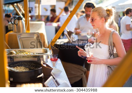 Beautiful blonde caucasian lady wearing white summer dress buying freshly prepared mealat a local food market. Urban international kitchen event taking place in Ljubljana, Slovenia, in summertime.