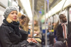 Beautiful blonde caucasian lady, wearing winter coat, traveling by metro in rush hour. Public transport.