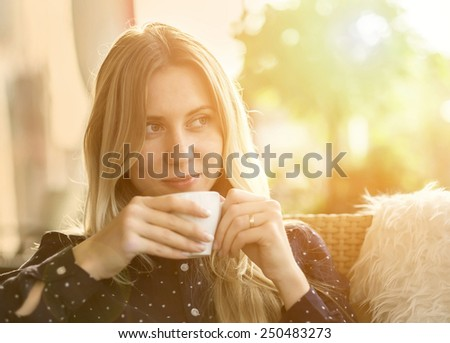 Beautiful blonde female drink coffee under sunlight #250483273