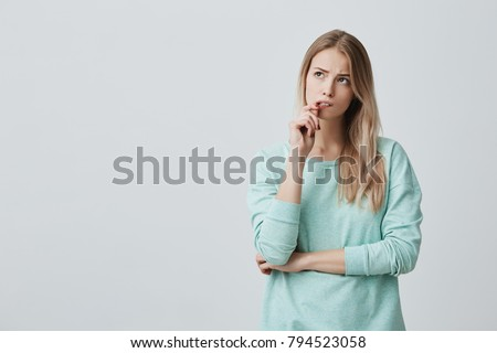 Beautiful blonde female with puzzled expression, keeps finger on lips, looks aside with bewilderment, poses against gray background. Body language and face expression