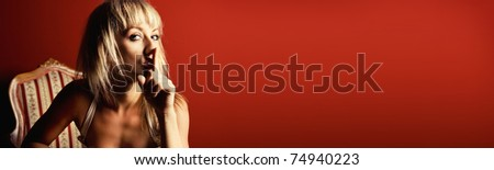 Beautiful blonde gesturing silence on red background (banner)