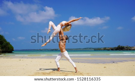 beautiful blonde girl and handsome man in white on the Pacific coast in Asia is engaged in acro yoga, pair acrobatics. duo acrobats circus performers dancers on the beach twine #1528116335