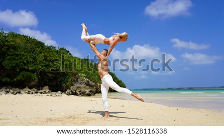 beautiful blonde girl and handsome man in white on the Pacific coast in Asia is engaged in acro yoga, pair acrobatics. duo acrobats circus performers dancers on the beach twine #1528116338
