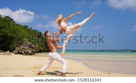 beautiful blonde girl and handsome man in white on the Pacific coast in Asia is engaged in acro yoga, pair acrobatics. duo acrobats circus performers dancers on the beach twine #1528116341