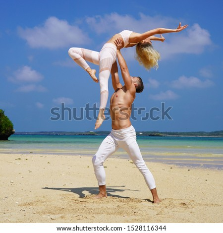 beautiful blonde girl and handsome man in white on the Pacific coast in Asia is engaged in acro yoga, pair acrobatics. duo acrobats circus performers dancers on the beach twine #1528116344