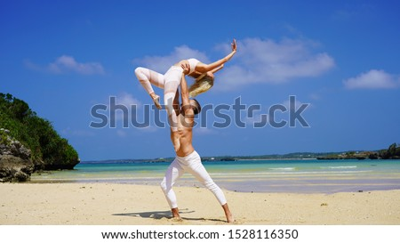 beautiful blonde girl and handsome man in white on the Pacific coast in Asia is engaged in acro yoga, pair acrobatics. duo acrobats circus performers dancers on the beach twine #1528116350