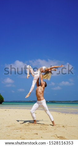 beautiful blonde girl and handsome man in white on the Pacific coast in Asia is engaged in acro yoga, pair acrobatics. duo acrobats circus performers dancers on the beach twine #1528116353
