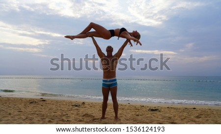 beautiful blonde girl and handsome man in white on the Pacific coast in Asia is engaged in acro yoga, pair acrobatics. duo acrobats circus performers dancers on the beach silhouette #1536124193