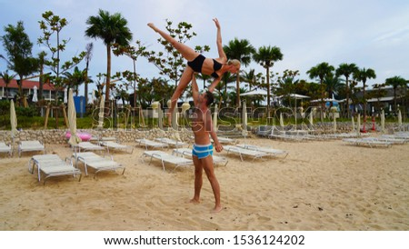 beautiful blonde girl and handsome man in white on the Pacific coast in Asia is engaged in acro yoga, pair acrobatics. duo acrobats circus performers dancers on the beach silhouette #1536124202