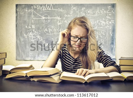 Beautiful blonde girl concentrated while studying at school