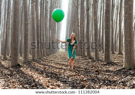 Beautiful blonde girl, dressed in green, laughing in the forest