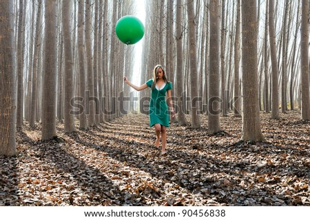 Beautiful blonde girl, dressed in green, walking into the forest