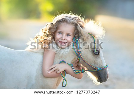 Beautiful blonde girl hugging pony. The same blue eyes.