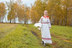Beautiful blonde girl in a traditional Slavic dress with a straw basket in her hands walks in the autumn forest