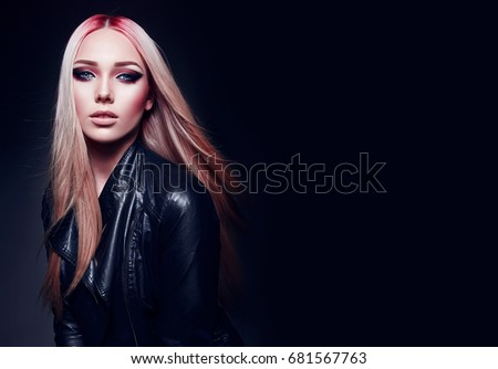 Stock Photo Beautiful blonde girl in black leather jacket and pink hair in rock style on black background.Makeup, cosmetics, hair care, hair dye, pink color. Fashion clothes. Fashion, beauty, rock, style, gothic.
