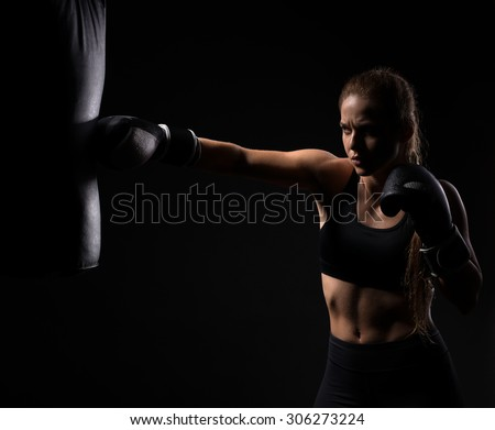 beautiful blonde girl in boxing gloves pushes the bag on a black background