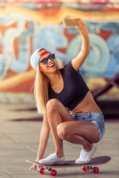 Beautiful blonde girl in glasses and cap is making selfie using a smartphone and smiling while standing on her skateboard in skate park