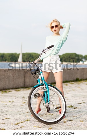 beautiful blonde girl in short white shorts, transparent top and sunglasses with cruiser bike at sea pier against yacht