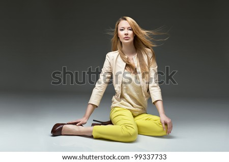 beautiful blonde girl in stylish clothes, yellow pants leather jacket and high heels. Fashion model posing at studio