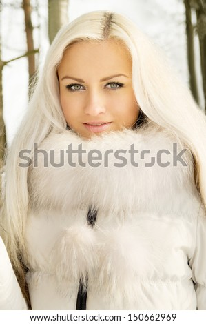 beautiful blonde girl in the forest in winter