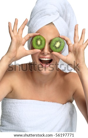 Beautiful blonde girl in towel takes kiwi before her eyes on white