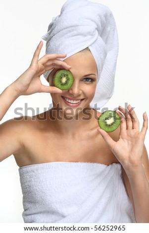 Beautiful blonde girl in towel with kiwi - on white