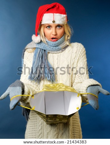 Beautiful blonde girl in winter clothes, santa hat with gift bag - stock photo