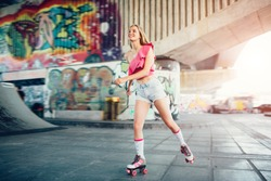 Beautiful blonde girl is riding in rollers in skate room. She is doing that very active. Girl wears pink top and shorts. She is happy.