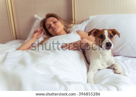 Beautiful blonde girl is sleeping in bed. Her cute dog is lying near and looking at camera #396855286