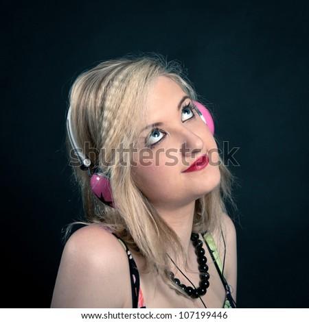 Beautiful blonde girl listening to music against dark background.