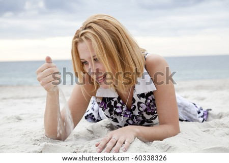 Beautiful blonde girl lying on sand at the beach in rainy day.