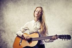 Beautiful blonde girl playing a classic guitar