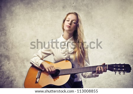 Beautiful blonde girl playing a classic guitar