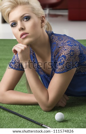 beautiful blonde girl plays golf with blue short dress and hig shoes, lying on the grass looks in to the lens with face on the left hand