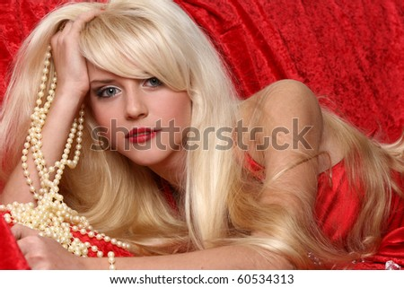 Beautiful blonde girl portrait on red background