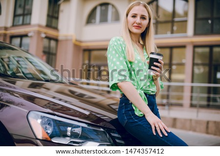Beautiful blonde girl sitting in the car driving listening to music and drinking coffee #1474357412