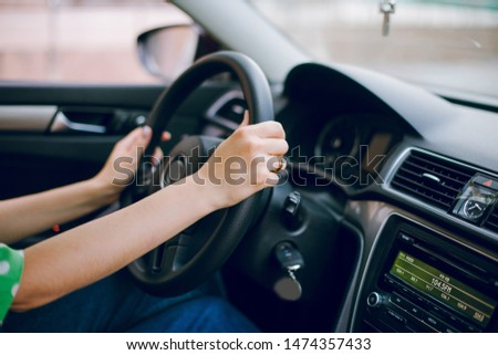 Beautiful blonde girl sitting in the car driving listening to music and drinking coffee