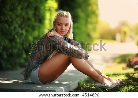 Beautiful blonde girl sitting on a green street. Shallow DOF.