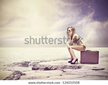 Beautiful blonde girl sitting on a suitcase