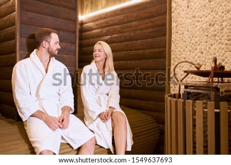 Beautiful blonde girl sitting on wooden bench together with impressive man, relaxing in hot sauna, chatting with pleasure, dressed in white dressing gowns, total relaxation concept
