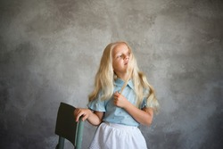 beautiful blonde girl stands near a chair against background of a gray wall. Photo demonstrating the character  child - daydreaming, enthusiasm, vulnerability, touching, beauty, stubbornness, cunning,