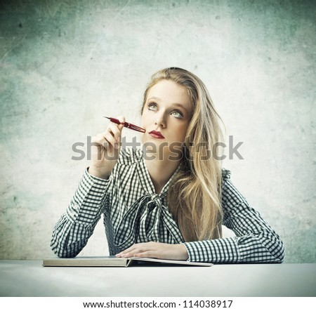 Beautiful blonde girl thinking while writing