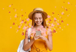Beautiful blonde girl using dating app with flying hearts on smartphone, yellow background