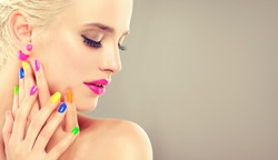 beautiful blonde girl with colorful manicure nails . Cosmetics,makeup and beauty