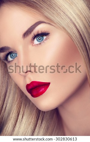 Beautiful Blonde Girl with Healthy blond Hair and perfect make up, beautiful skin. eye makeup, long eyelashes. Closeup of Beauty Woman face make up. Bright make-up with sexy red lips and perfect skin