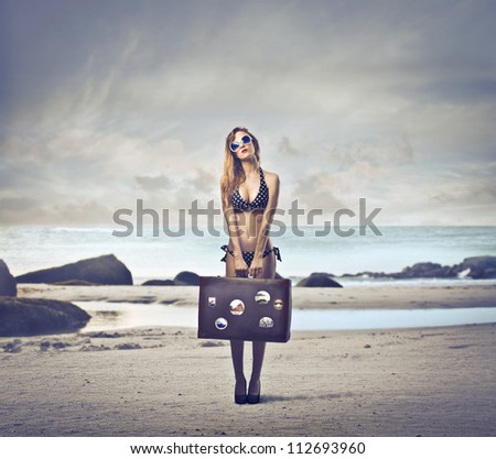 Beautiful blonde girl with her luggage on a beach