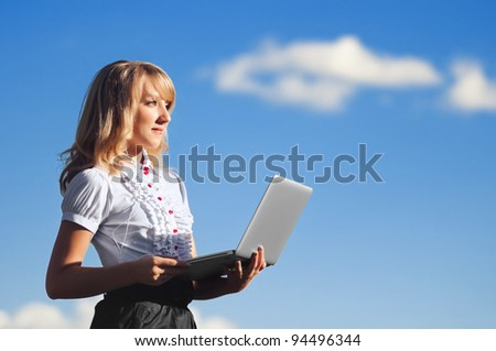 Beautiful blonde girl with laptop working outdoors