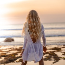 Beautiful blonde girl with long hair in short white dress walking at sunset on the beach in Bali, Indonesia