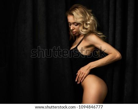 Beautiful blonde girl with long legs in black bodysuit against black velvet curtains in white sneakers. #1094846777